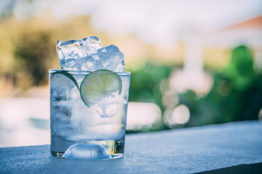 liquid, ice, and lemon slice in clear drinking glass